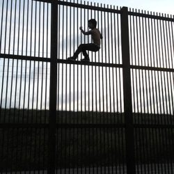 photo of child scaling Meixico/US fence