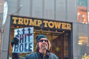 King Trump's tower with man holding shithole sign.